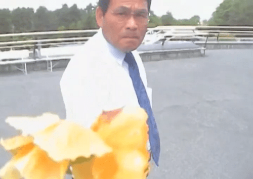 a scene of a man who receives yellow flower from a stranger in Aijo short film